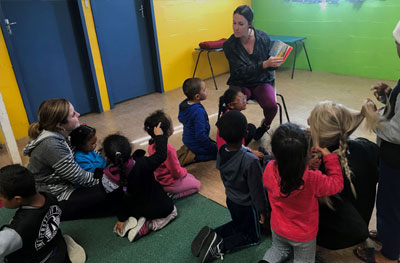 CMU students read and work with students in a classroom