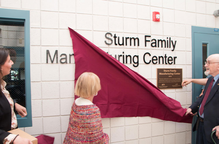 Individuals unveil the new Sturm Family Manufacturing Center sign
